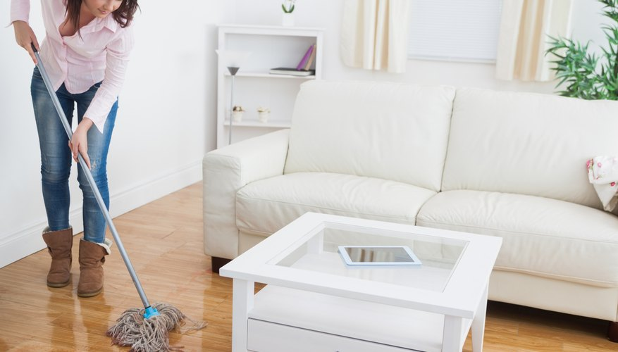 A woman mopping her living room floor.