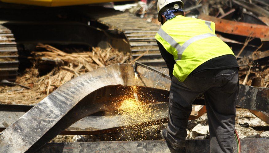 A worker cuts a steel beam at a demolition site.