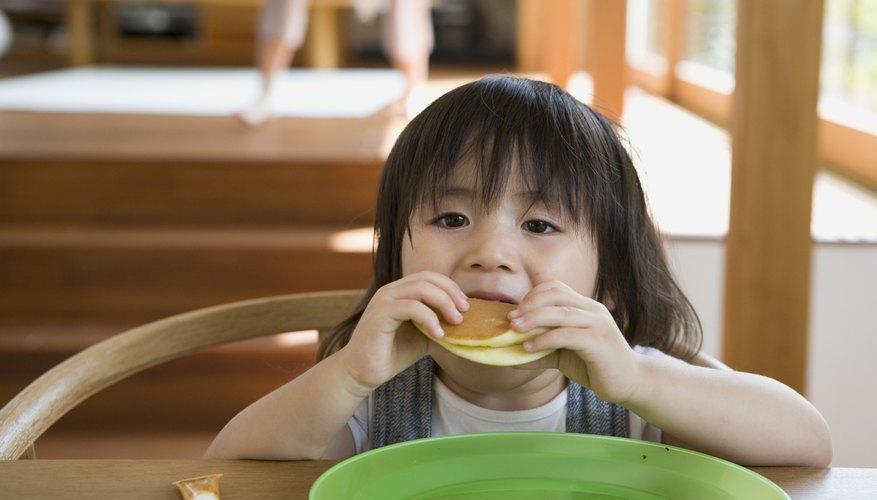 A toddler eats her pancakes.
