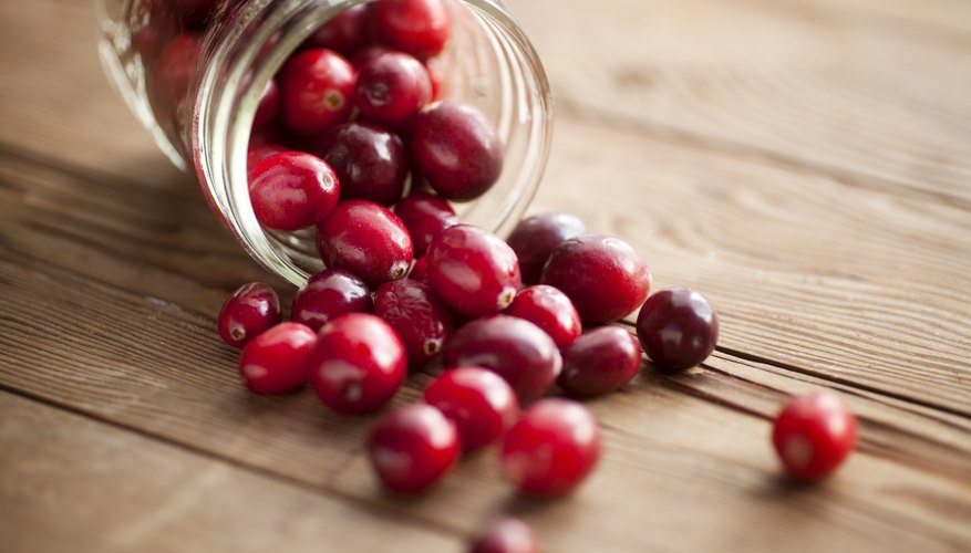 Cranberries spilling out of a jar onto a wooden table
