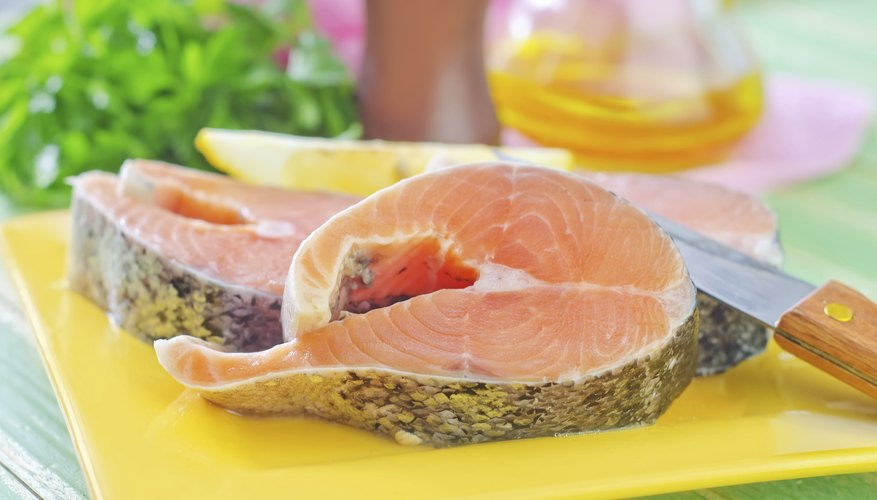 Two pieces of raw salmon on plate in kitchen