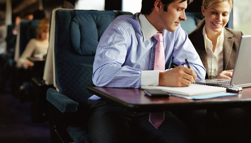 Businessman and businesswoman using laptop on train, smiling