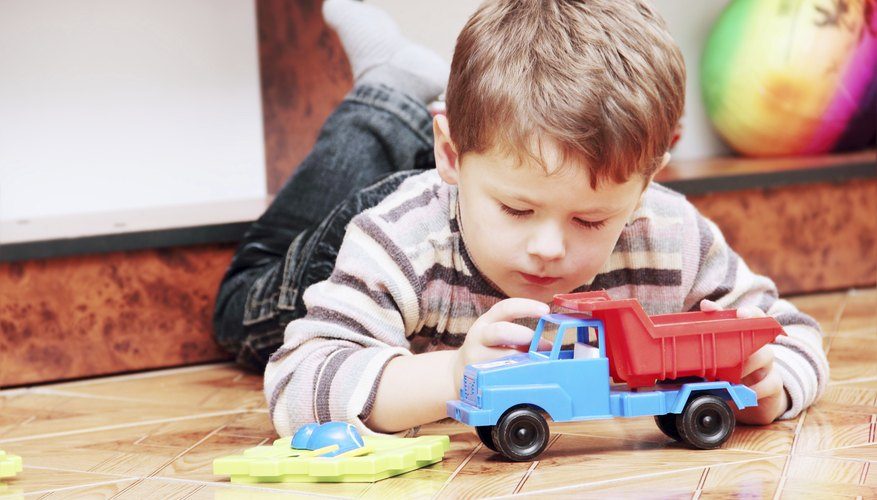 Young child playing with toy truck
