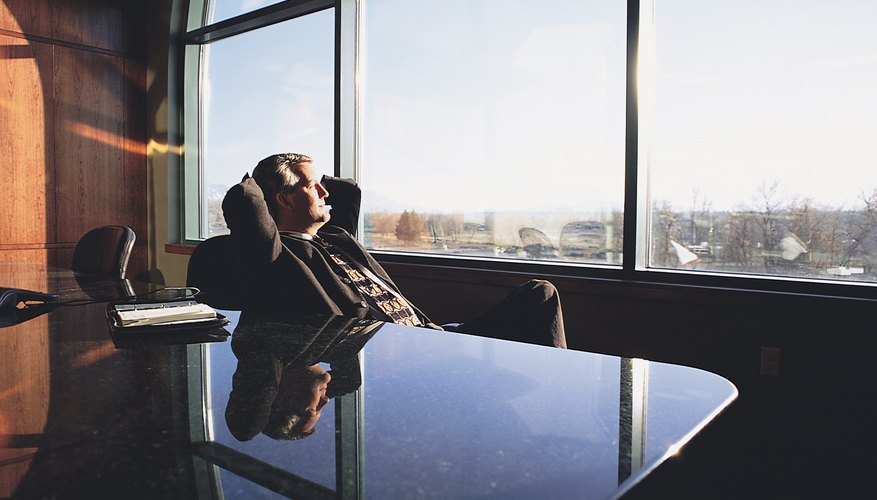 A RELAXED EXECUTIVE IN A SUIT RECLINES IN A CHAIR IN AN OFFICE AS HE LOOKS OUT ON THE CITY