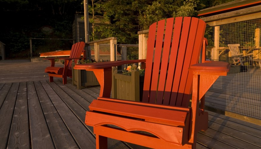 An adirondack chair on a garden patio at sunset.