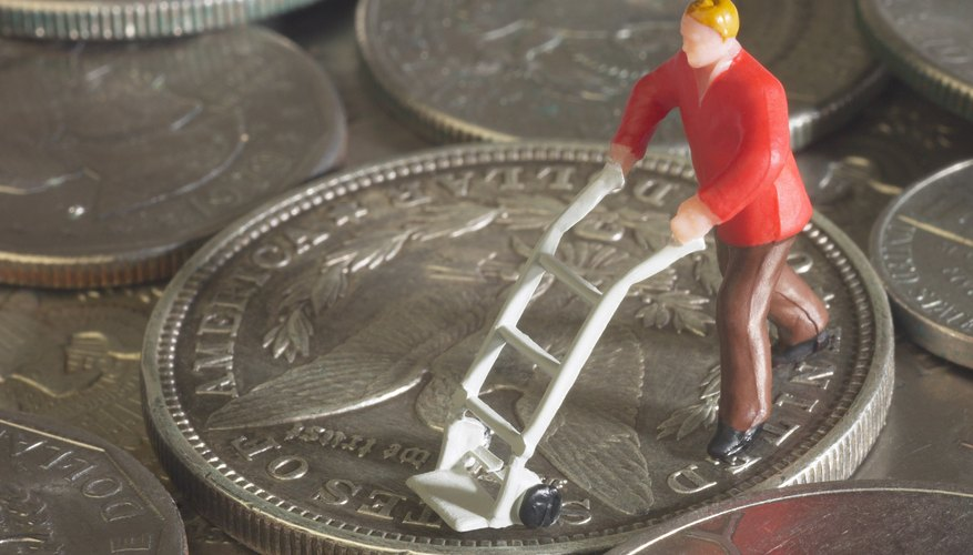 Figurine with miniature hand truck on coins