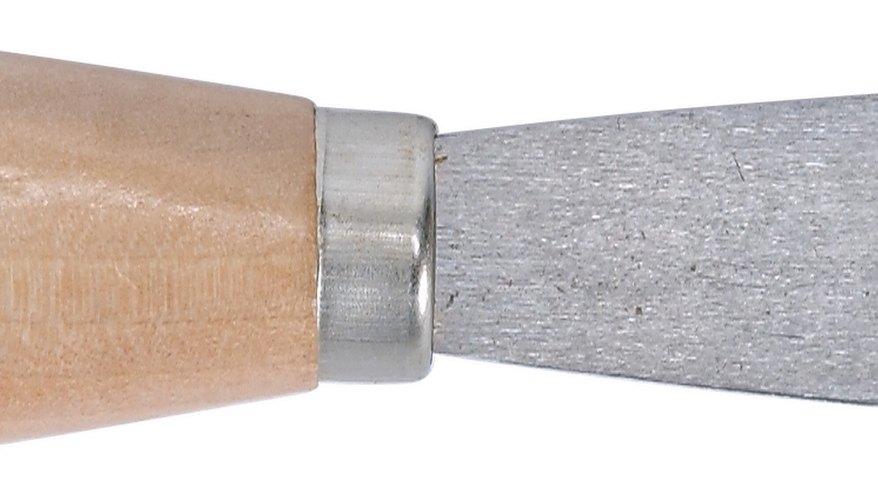 Usa una espátula para rellenar las grietas con masilla.