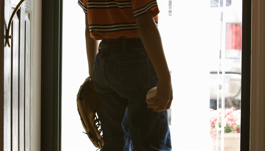 Boy with baseball, mitt, and cap looking out front door