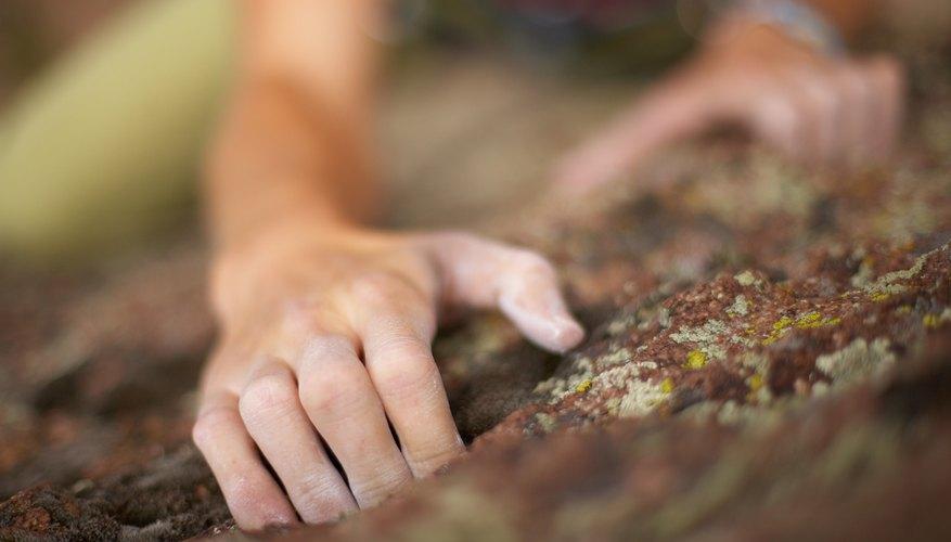 A woman climbs a rock face.