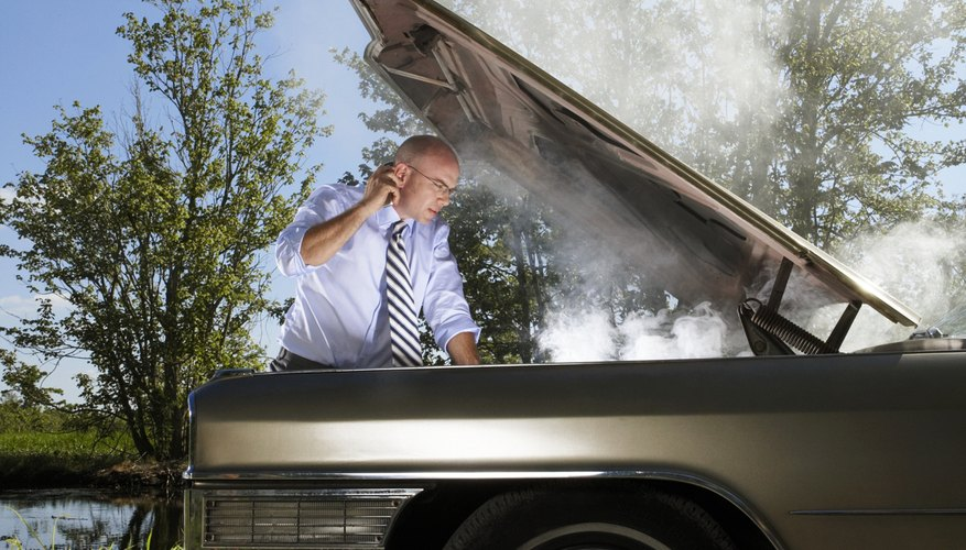 Businessman on rural road looking under steaming car bonnet