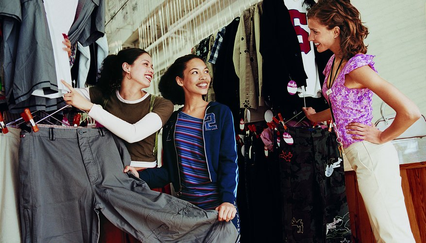 Two Young Girls Looking at Trousers in a Clothes Shop With a Smiling Saies Assistant Standing Nearby
