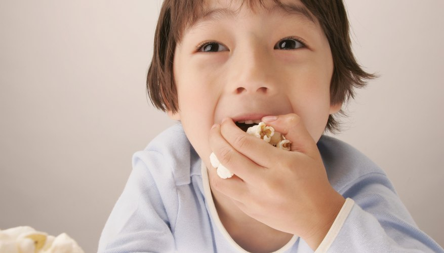 Young boy eating popcorn