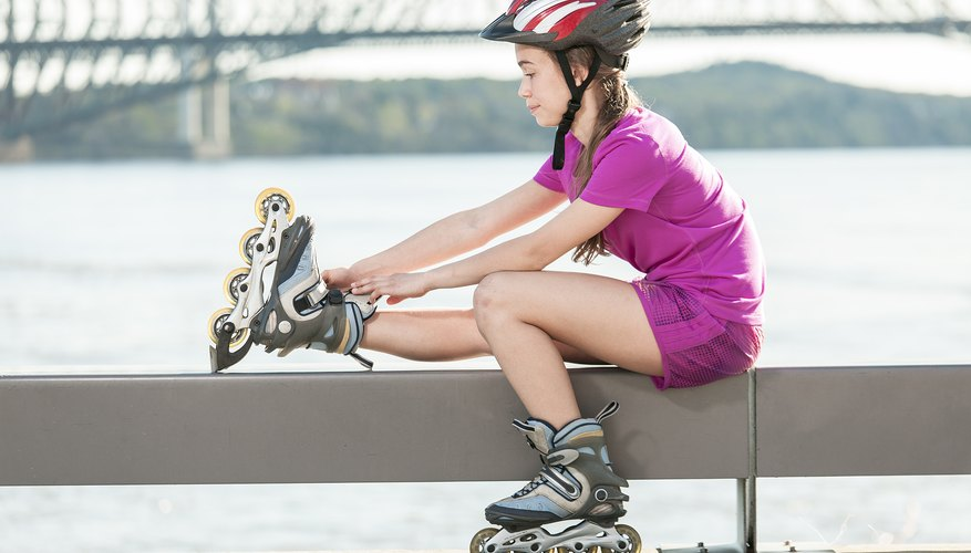 A girl adjusting her inline skate on a bench near the water.