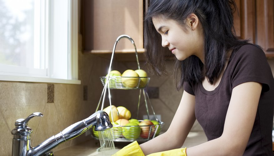 Teenager washing dishes in kitchen.