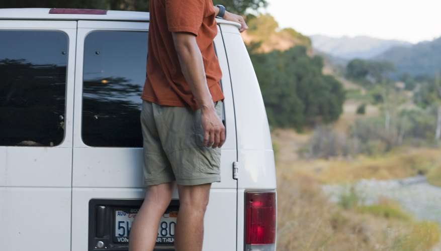Man standing on the bumper of a van.