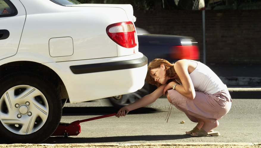 Woman about to lift automobile with hydraulic jack