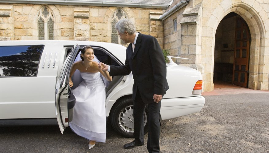 Father helping bride out of limousine