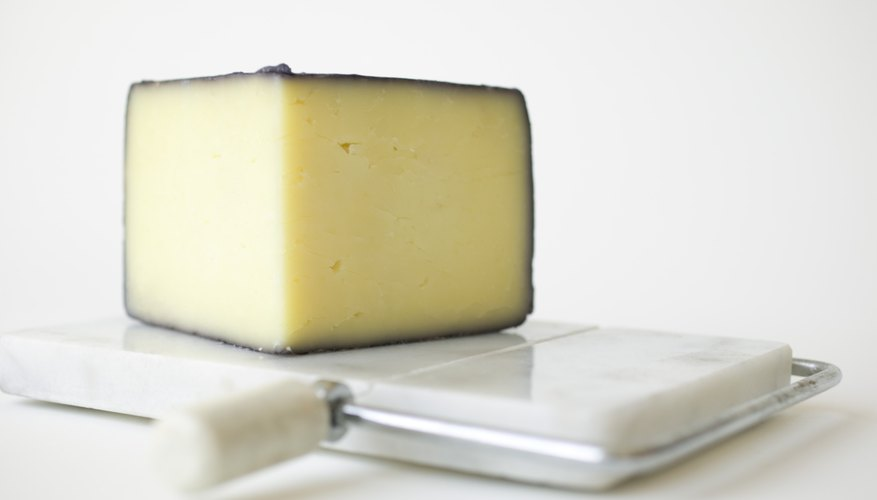 A wedge of cheese on a cutting board.