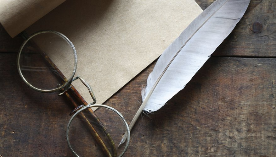An overhead view of a quill, scroll and eyeglasses on a table.