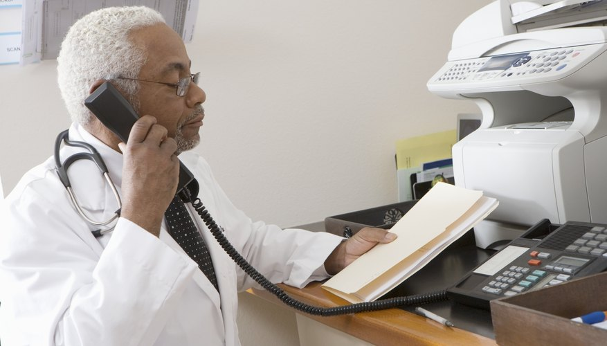 African American senior male doctor holding document while using phone