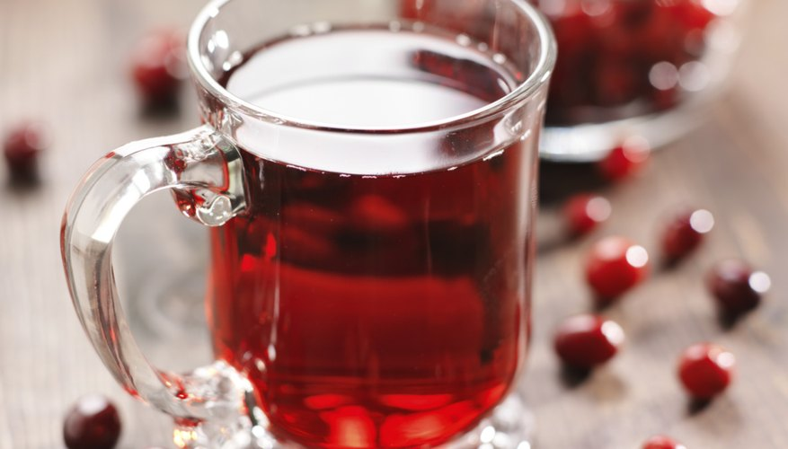 A glass cup of cranberry juice and cranberries on a wooden table