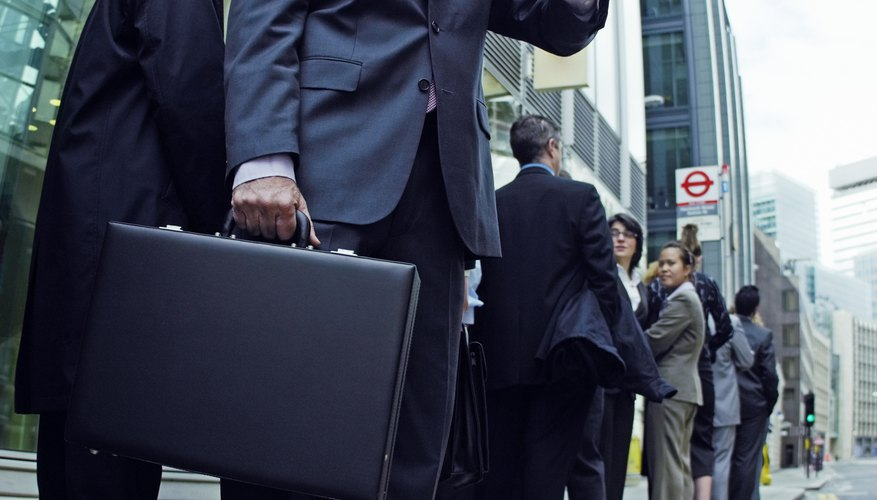 Businessman Looking at his Watch While Standing at the end of a line of People at a Bus Stop