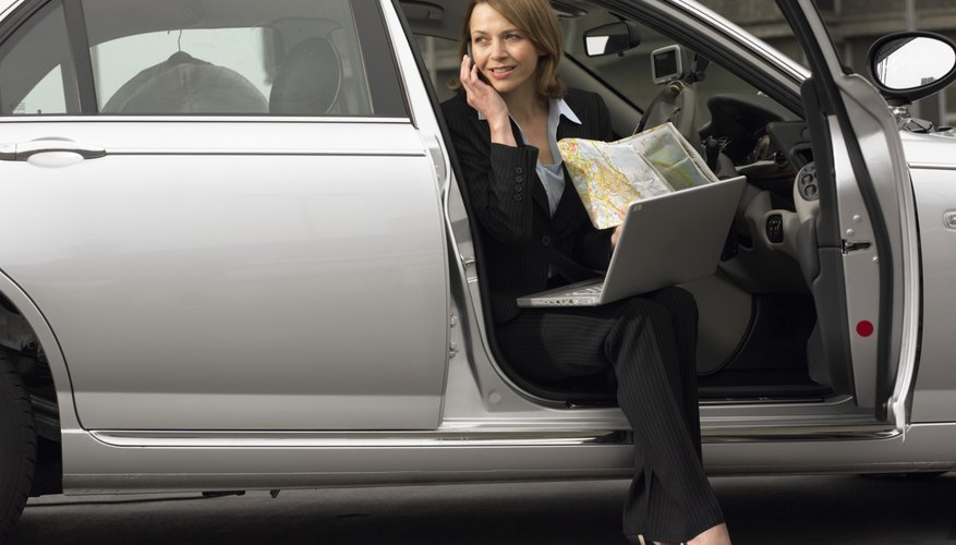 Businesswoman Sitting in Her Car Using a Mobile Phone With a Laptop and a Map