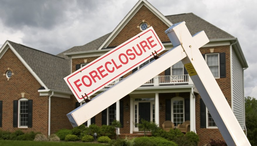 A house with a foreclosure sign in front.