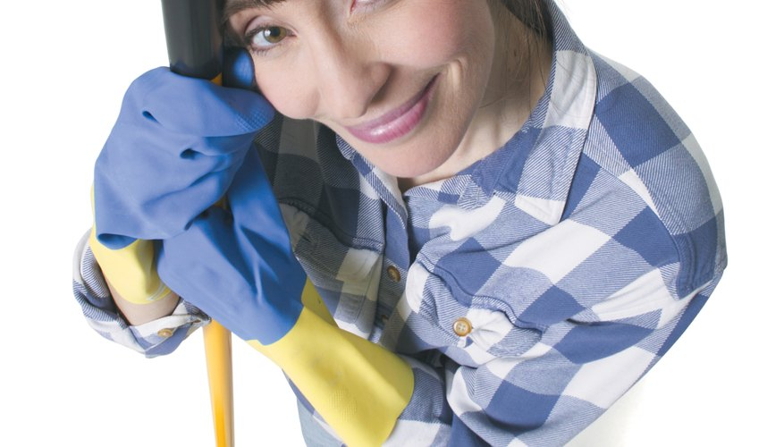 a caucasian woman in jeans and a plaid shirt wears rubber gloves and holds a mop as she looks up into the camera
