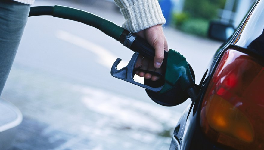 person filling petrol in a car gas tank