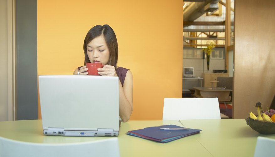 Businesswoman sitting in front of a laptop drinking coffee