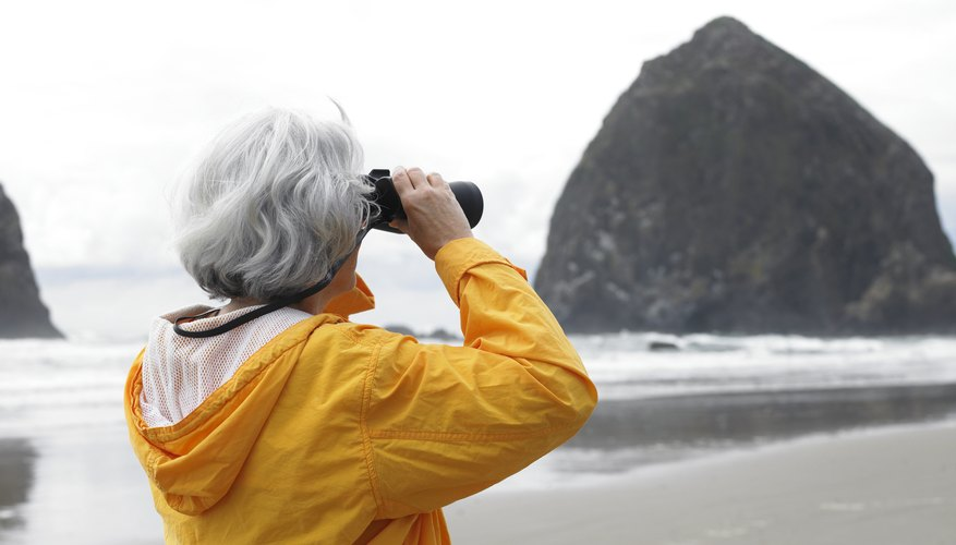 Woman holding up binoculars.