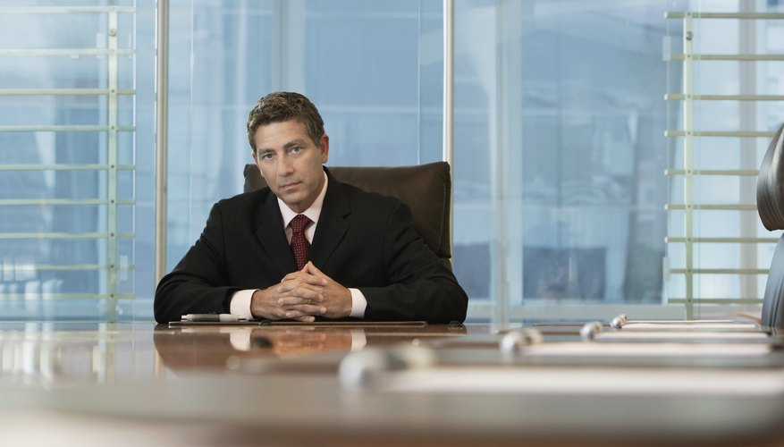 Serious Businessman Sitting At Conference Table