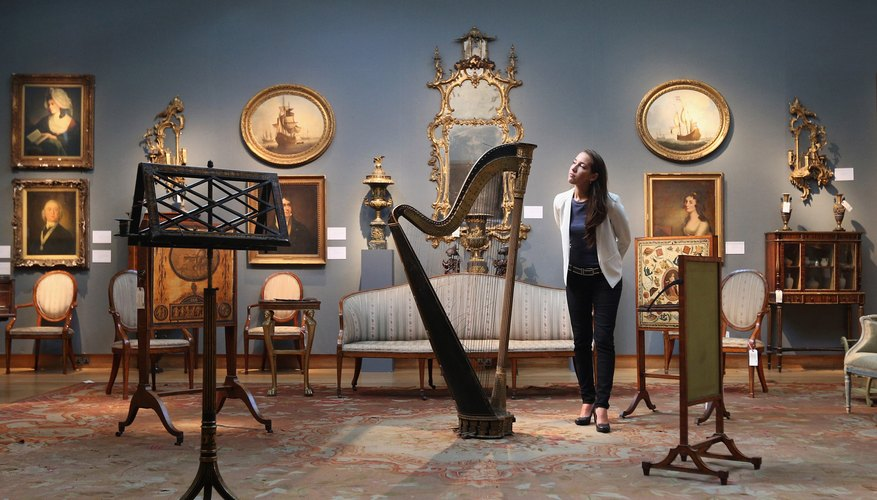 A Christie's Auction House assistant admires a Regency double-action harp before its auction in London in 2013.