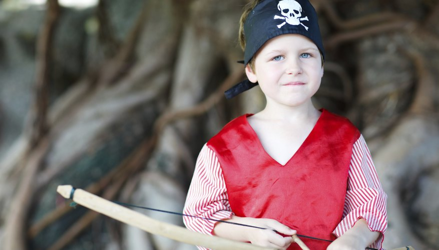 A boy dressed as a pirate holding a bow and arrow.