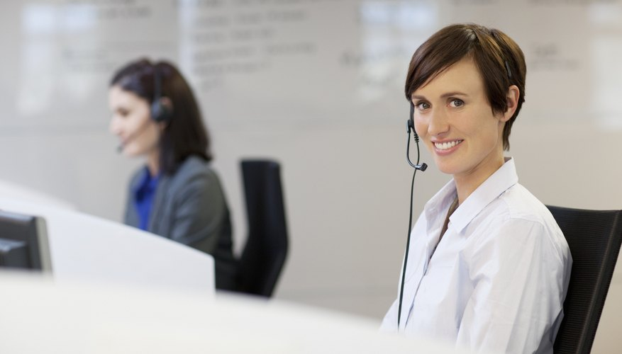 Smiling salespeople on the phone using headsets.