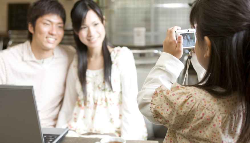 A young girl taking a digital photo of her parents at home.