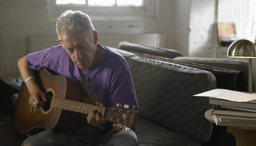 Mature man playing an accoustic guitar on a sofa.