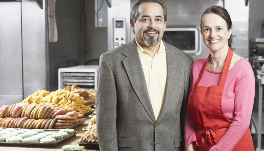Portrait of a female baker smiling with a businessman in a bakery