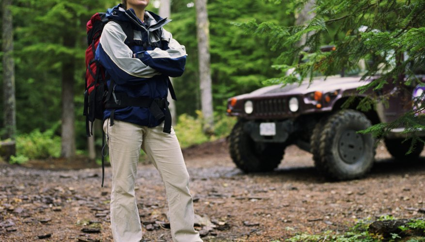 Young woman standing in front of off road vehicle in forest, portrait