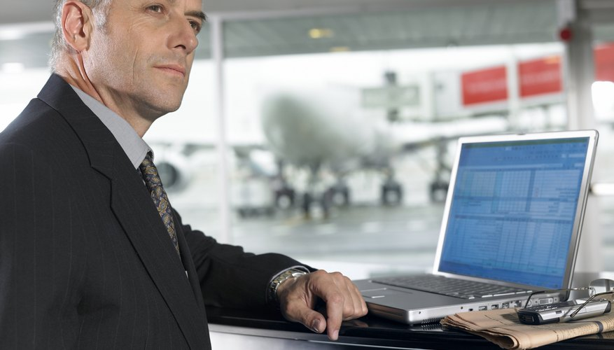 Businessman working on his laptop at airport.