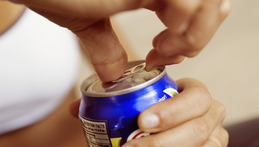 A woman opens a can of soda.