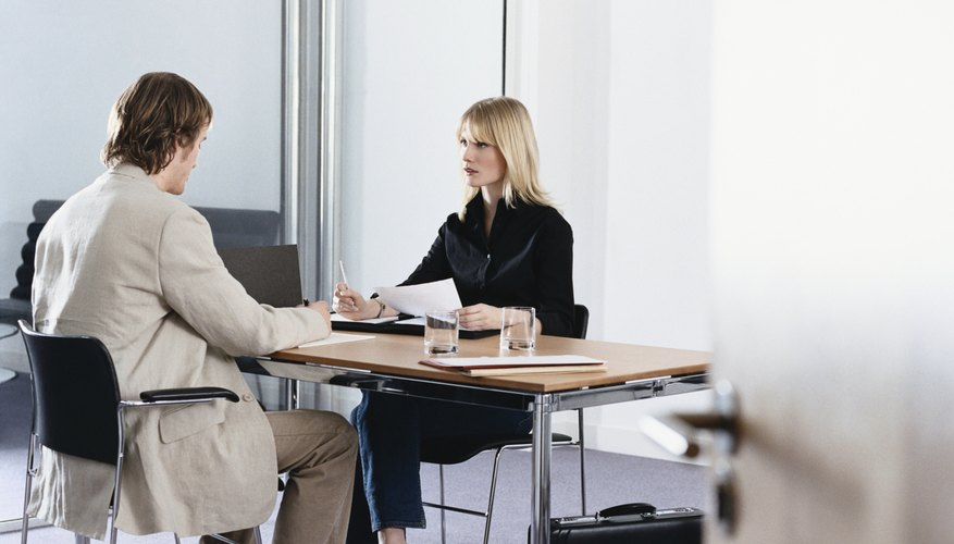 Businessman and Businesswoman Sit Opposite Each Other at a Table in an Office, Having a Discussion