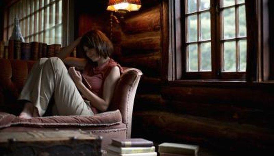 Mujer leyendo un libro en su sofá.