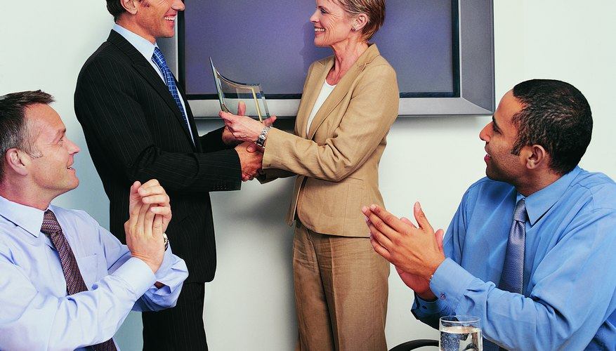 Businesswoman Shaking Hands and Holding an Award With Her Colleagues Applauding Her