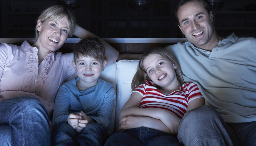 A family sitting on a sofa watching a DVD.