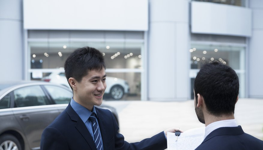 Salesman selling a car to young businessman