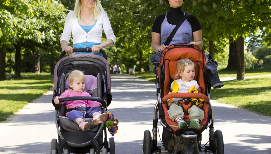 Mothers pushing two young children in strollers.