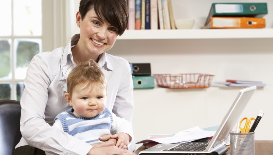 Woman working at home with a baby on her lap.