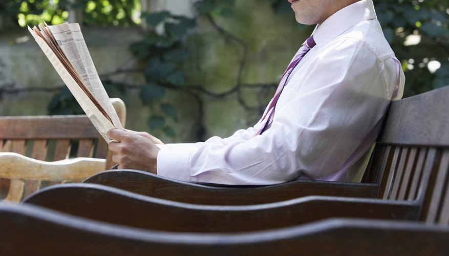 Businessman sitting on bench in park garden reading paper, mid section